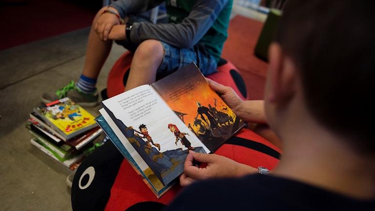 Några barn och vuxna sitter och läser i barnböcker.