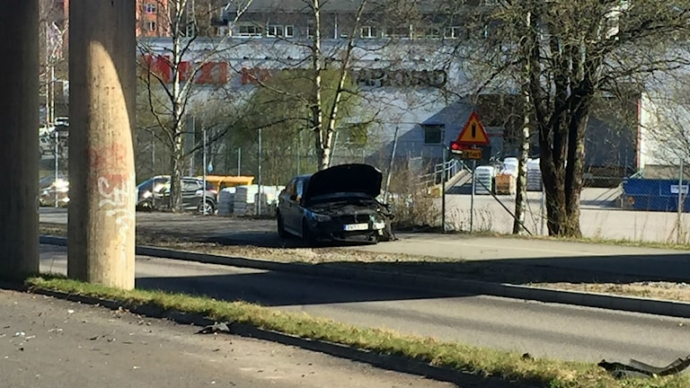 En bil med motorhuven uppe står på gångbanan på Lars Kaggsgatan i Borås.