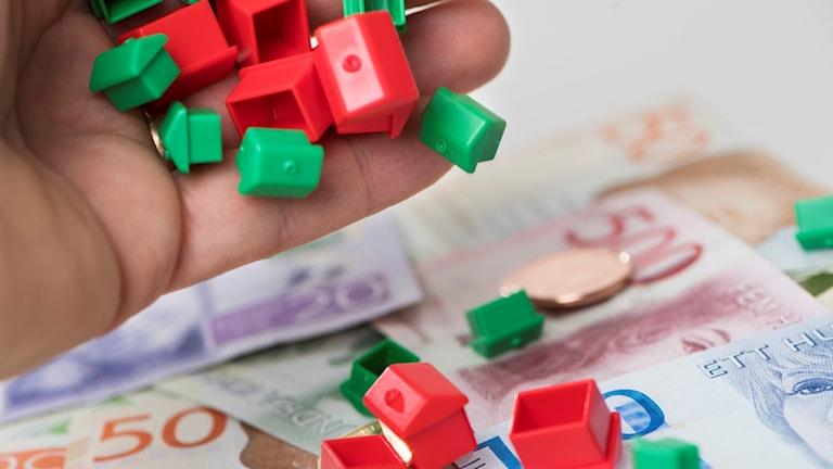 Sedlar och en hand som håller miniatyrhus från spelet Monopol.