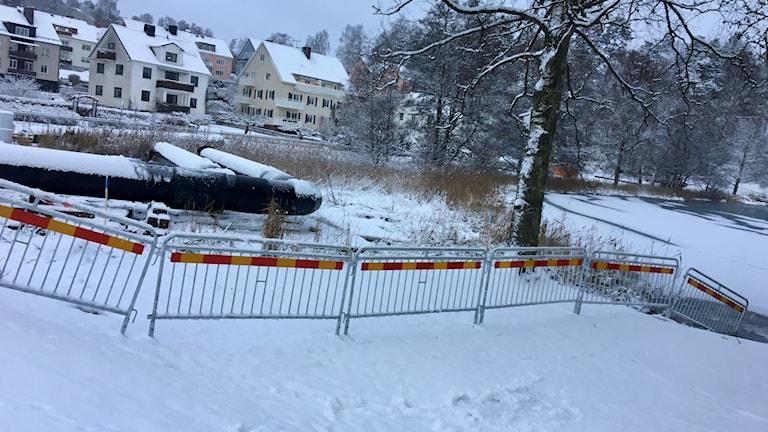 Stora svarta rör ligger på marken vid en sjö täckt av snö
