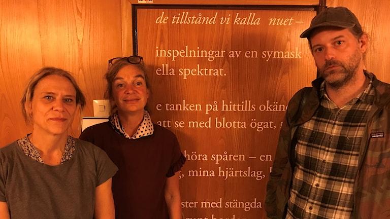 Två kvinnor och en man framför en trädörr med vit text på.