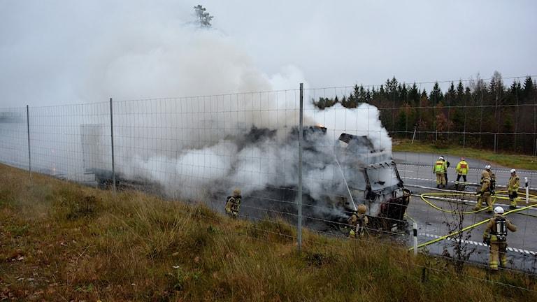 En rökfylld lastbil och räddningstjänstpersonal på en väg