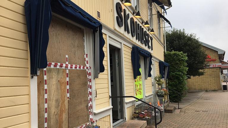 Skyltfönstret till butiken i ett gult trähus är förbommat med masonitskivor.