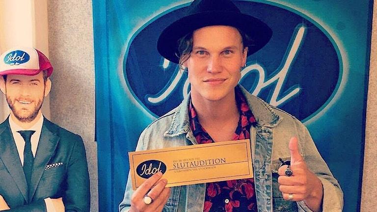 Sebastian Dahlström i svart hatt och jeansjacka håller upp guldbiljetten och gör tummen upp.