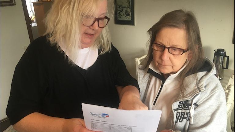 Två kvinnor tittar på ett papper.