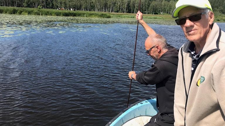 Ute på sjön i en båt syns två män på bild. En av de har satt ner ett armeringsjärn i vattnet för att mäta slamdjupet.