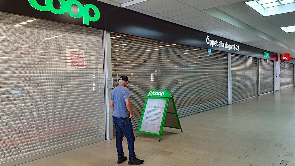 Bild med en man framför en stängd Coop-butik.