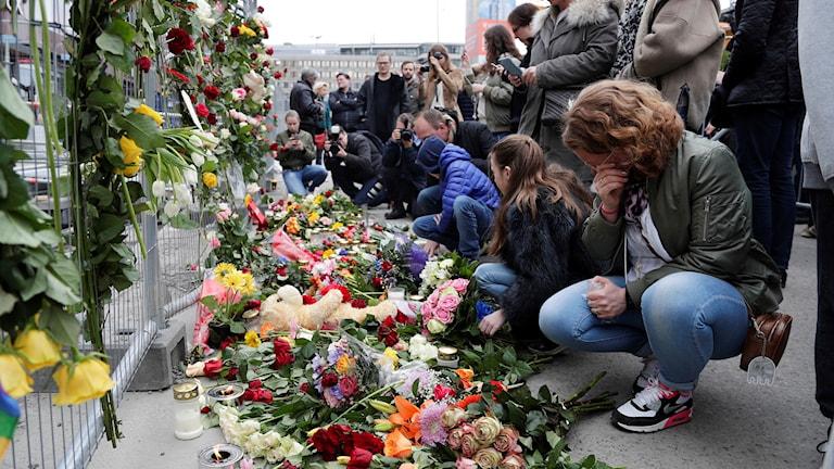 En rad människor sitter på huk och är ledsna, en del gråter. De sitter framför staket fyllda med olika blommor.