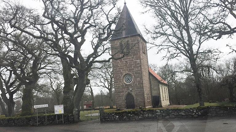 Asklanda kyrka är byggd i gulbrun sten och har ett torn med spetsigt tak.