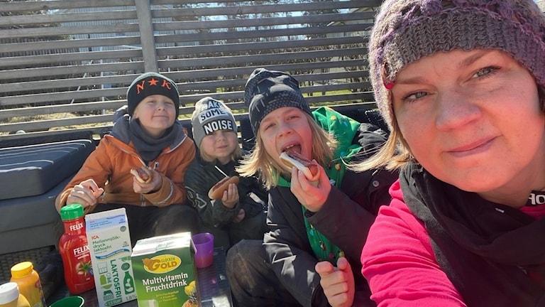 En mamma och hennes tre barn sitter utomhus och äter grillad korv.
