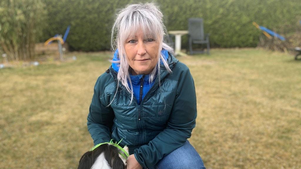 Monia Wergård sitter på gräsmattan tillsammans med en av sina hundar.