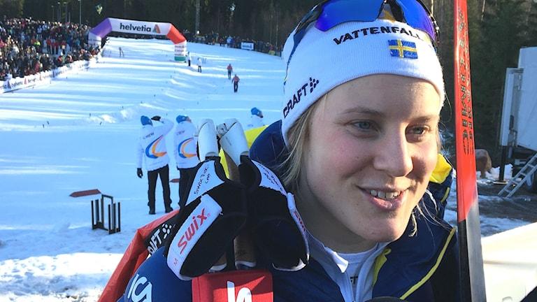 Hann Falk iklädd landslagskläder står till höger i bild, bakom syns skidspåren på Lassalyckan i Ulricehamn