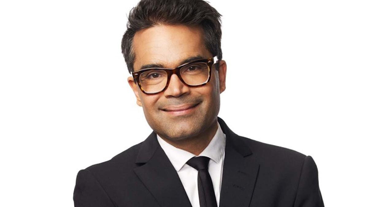 David Batra är klädd i svart kostym, med vit skjorta och svart slips. Han bär glasögon, har mörkbrunt hår och är brun i hyn.