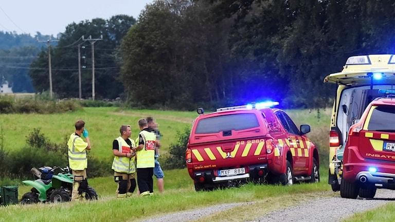 Räddningstjänst tar hand om skadade, intill en grön fyrhjuling.