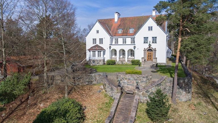 En lång stentrappa leder upp till den ståtliga villan omgiven av tallar och en stor trädgård.