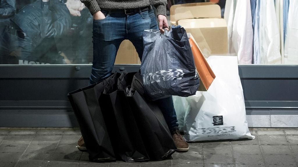 En kille står med shoppingkassar.