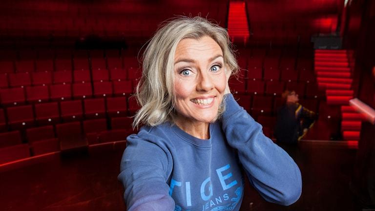 Anna Carlsson står framför en tom teatersalong.