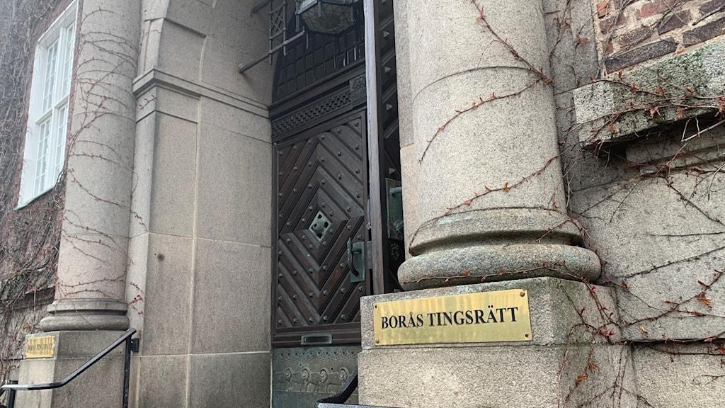 Porten till Borås Tingsrätt. Den bruna porten är öppen och en guldig skylt där det står Borås Tingsrätt är placerad på båda sidor porten.