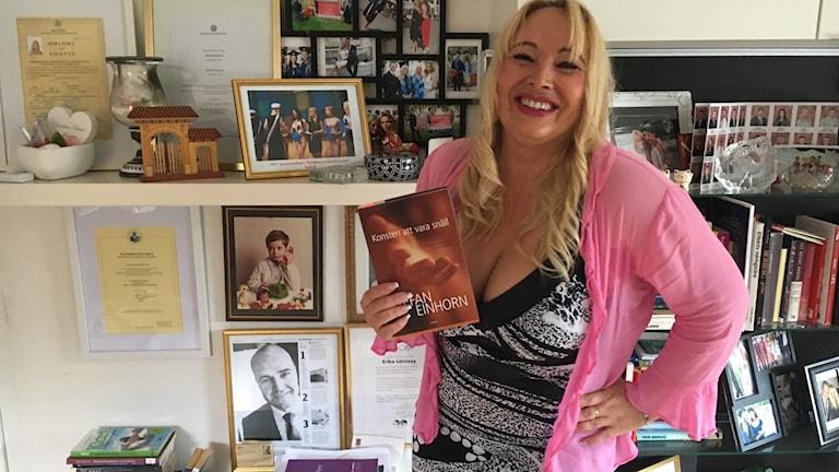 Kvinna i rosa tröja står vid bokhylla och håller bok