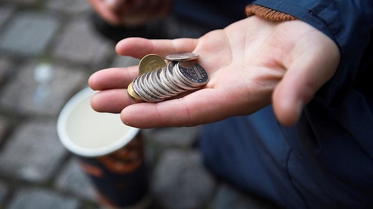 En hand håller mynt.