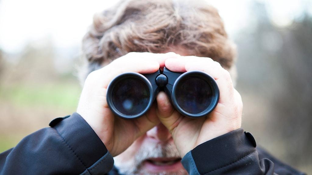 man med kikare tittar mot dig