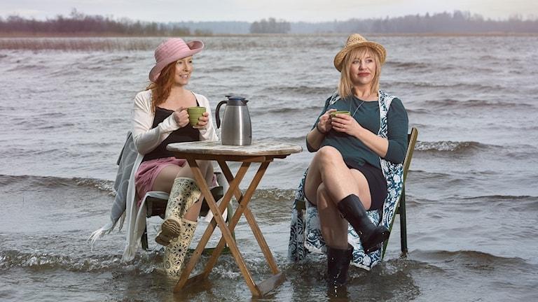 Två kvinnor sitter vid ett bord som står i vatten i en sjö
