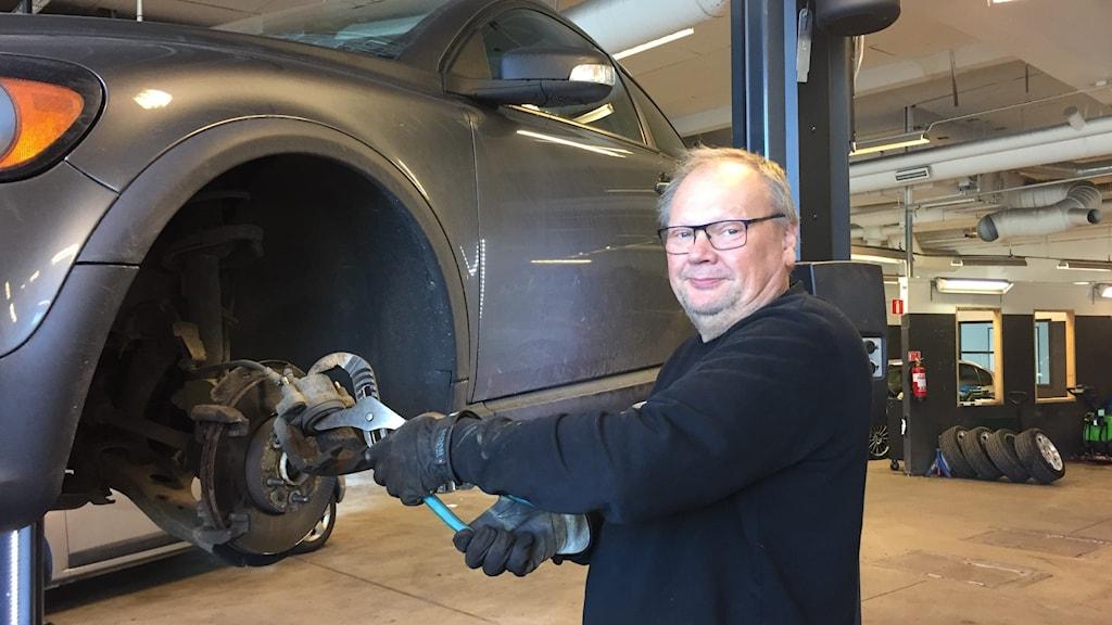 Roger Rudenbrandt ler mot kameran när han visar hur han renoverar bromsarna på en bil som är upphissad på billyften