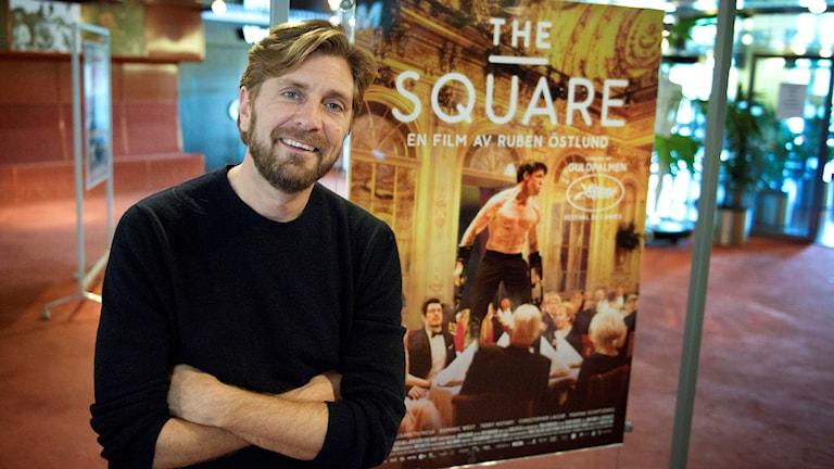 """Ruben Östlund i svart tröja och mellanblont hår och skägg ler mot kameran. Bakom finns en bild från filmen """"The Square""""."""