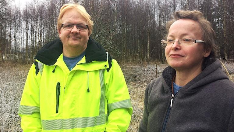 Till vänster i bild Tony Einarsson iförd gul reflexjacka, till höger Mia Einarsson, de står utomhus med frostigt gräs och björkar i bakgrunden.
