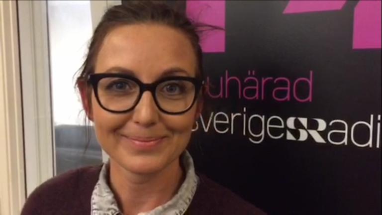 En kvinna med glasögon ler framför en roll-up med text P4 Sjuhärad