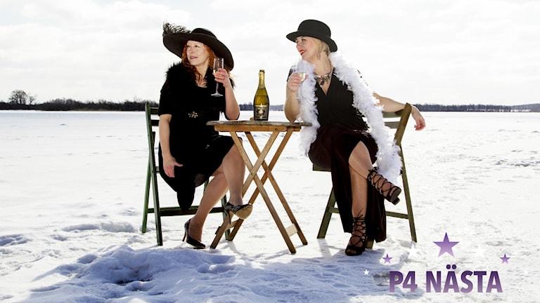 The Flying Bumblebees, två kvinnor, sitter vid ett cafébord och dricker mousserande vin i ett snötäckt landskap.