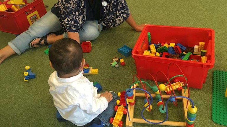 Ett barn leker med lego på golvet