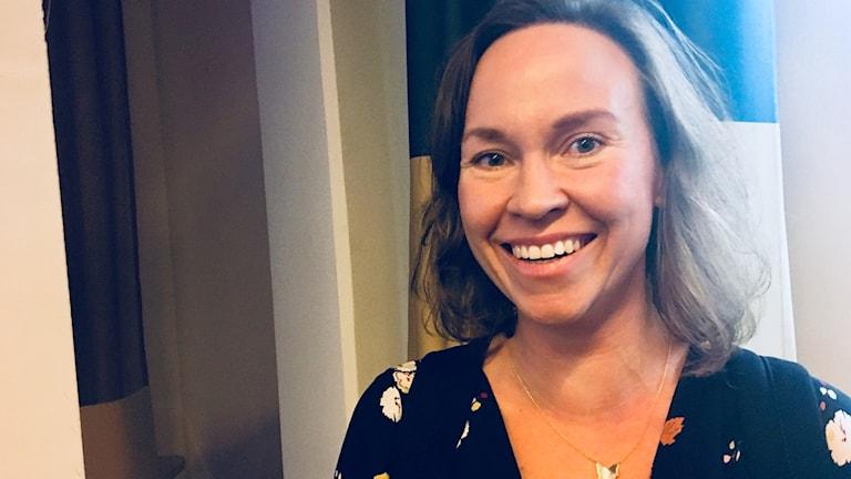 Ida Wickström tittar in i kameran med ett brett leende.