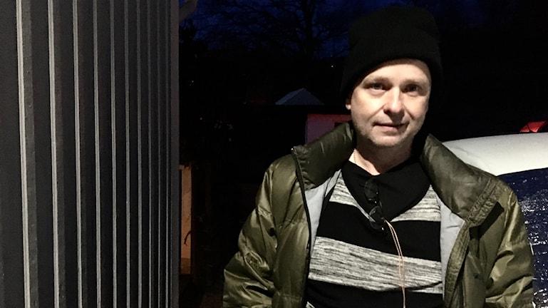 Kamil Svajda står utomhus i mörkret framför sin vita bil. Hans ansikte är upplyst av en lampa på husväggen intill honom till vänster.
