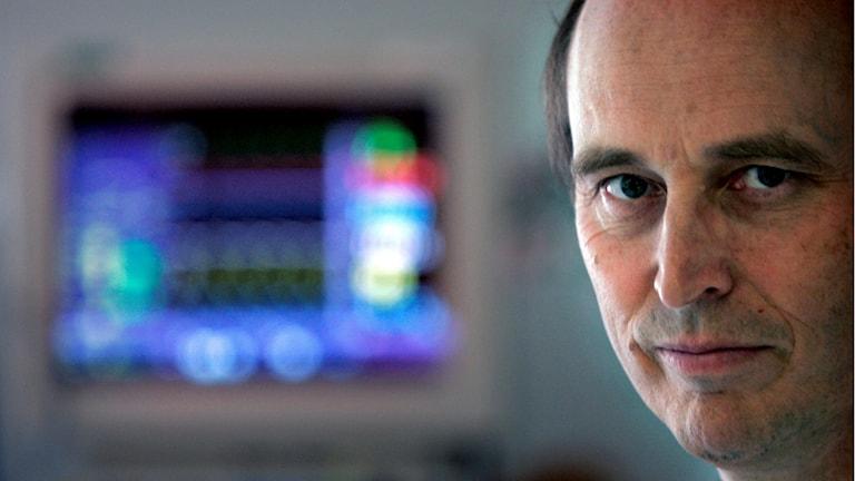 Ansiktsbild på man med monitor i bakgrunden.
