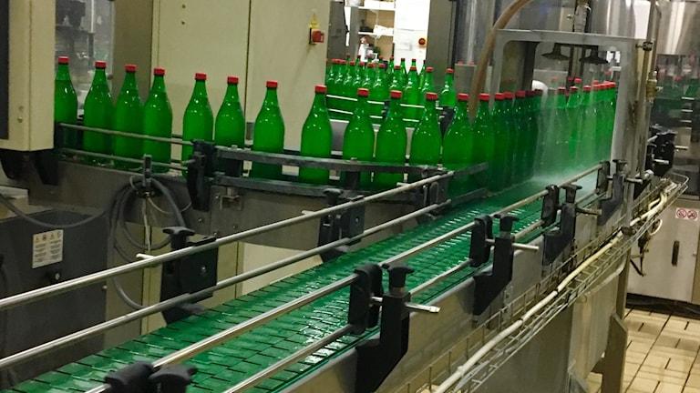 Drickaflaskor på ett rullband