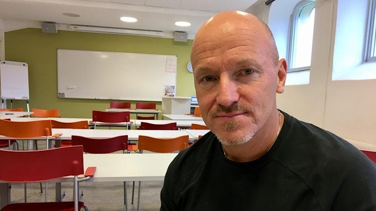 Förskolechefen Fredric Gieth sitter i en sal med bänkar, bord och en vit tavla bakom sig.