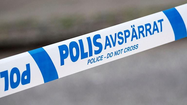 Blå-vitt avspärrningsband med polisens logga.