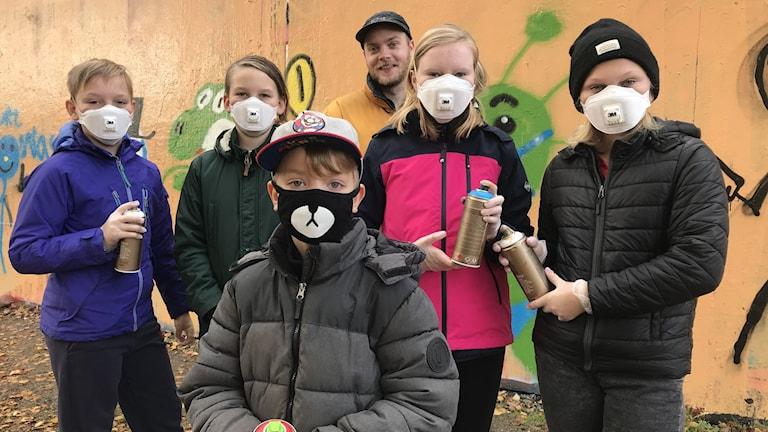 En grupp barn och graffitikonstnären Adam Algotsson framför den öppna väggen på Magasinsgatan.