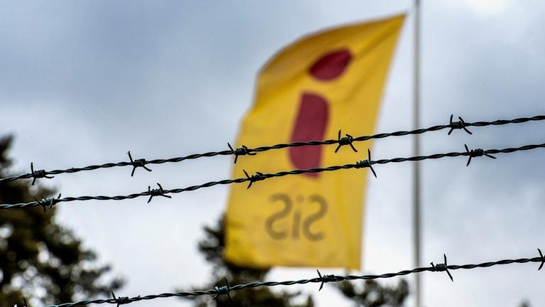 """En gul flagga med ett rött """"i"""" och texten """"SiS"""" i svart fladdrar bakom tre rader taggtråd."""