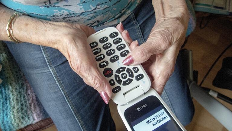 ÄLDRE KVINNA MED TELEFON