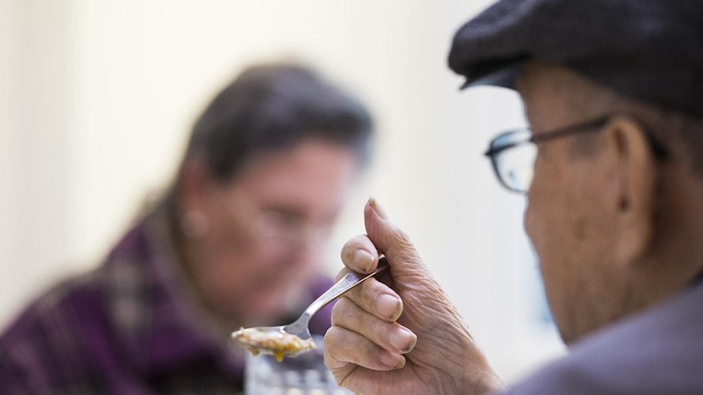 En äldre man i keps äter med sked.