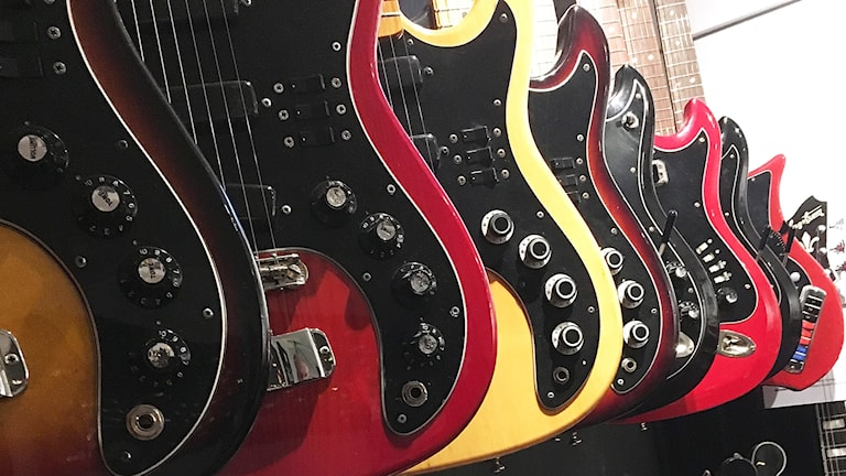 Elgitarrer i brunt, flera nyanser av rött, gult och svart hänger på väggen.