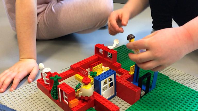 Två barnhänder leker med en legofigur i ett legohem.