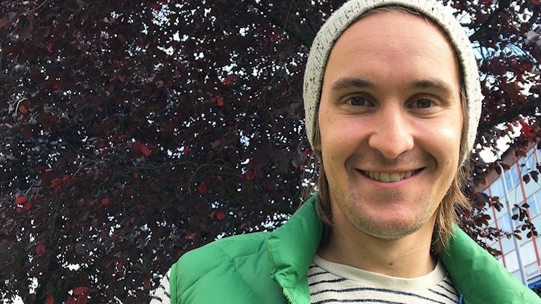 En kille med stickad mössa och grön jacka framför ett träd med vinröda löv.