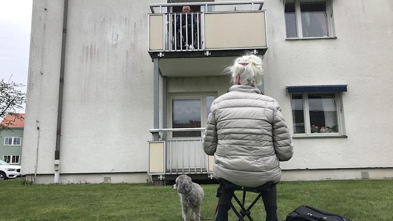 En äldre kvinna sitter på en tältstol utanför ett äldreboende där hennes man sitter på balkongen.