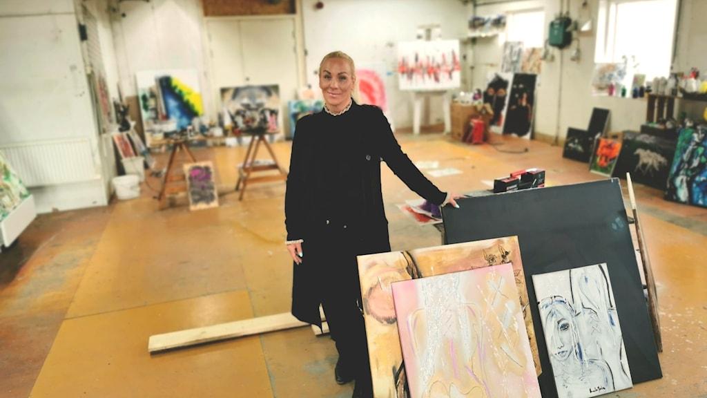 Anna Jansson i sin ateljé, omgiven av målningar och konstnärsmaterial.