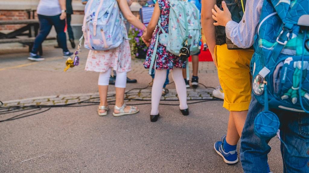 Barn med skolväskor utanför skolan.