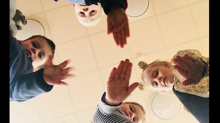 """Elliot Oscarsson, Hugo Simonsson, Whilma Svensson och Alva Dalmyr står över kameran och håller upp en hand för att visa """"stopp""""."""