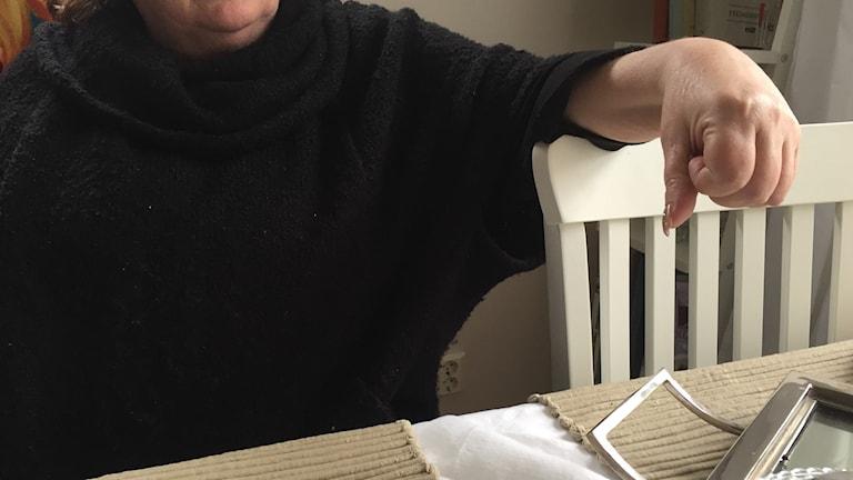 Bröstbild på person i svart tröja, taget från hakan och nedåt.